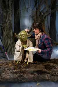 Madame Tussauds artist Katie Ashton puts the final touch to Yoda¹s wax figure in an atmospheric recreation of his Dagobah swamp scene