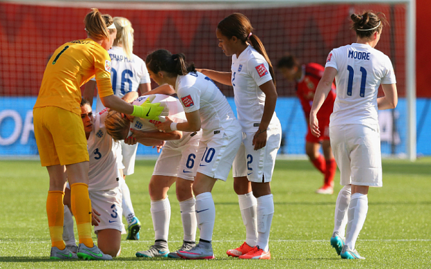 Laura Bassett is consoled by teammates after her 93rd-minute own goal put Japan into the World Cup final