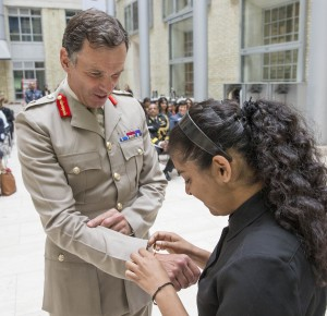 Pictured:Miss Radhika Keshav from the National Hindu Students Forum ties a rakhi onto the wrist of Lieutenant General Gregory, Chief of Defence Personnel.