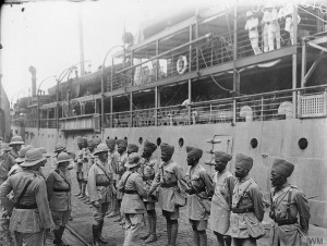 A group of British soldiers bidding farewell to Indian officers in a dock.