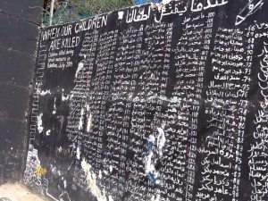 A wall in a refugee camp lists the names of children who have been killed