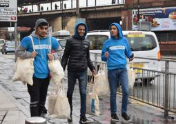 Young volunteers distribute hot food and drinks to homeless during Christmas period